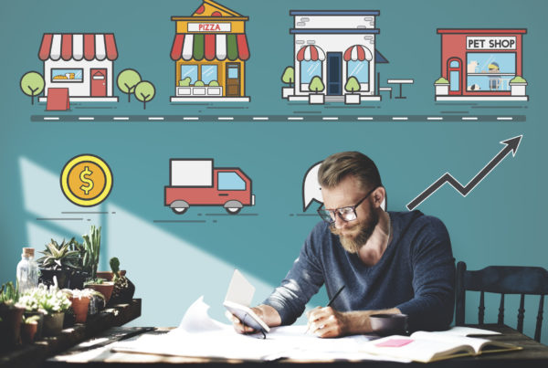Young Business Owner reading strategy documents with Icons floating above head of local generic business shops